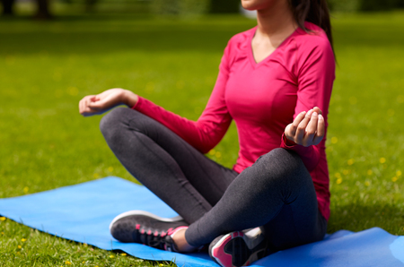 athletic: sport, meditation, yoga, fitness and people concept - close up of woman meditating on mat at park Stock Photo