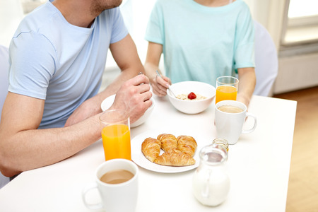 food, eating, people and healthy food concept - close up of couple having breakfast at home photo