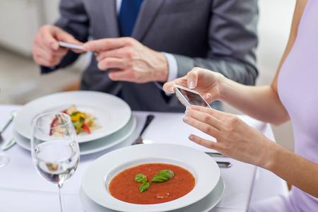 lunch: la gente, el ocio, la alimentaci�n y la tecnolog�a concepto - cerca de la pareja con smartphones toma el cuadro de la comida en el restaurante Foto de archivo