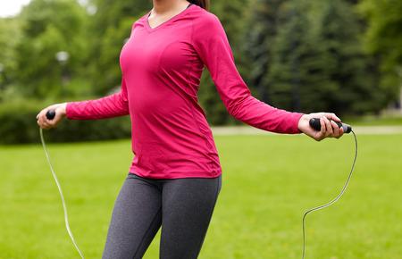 jump rope: fitness, deporte, entrenamiento, la gente y el estilo de vida concepto - cerca de la mujer afroamericana ejercicio con saltar la cuerda al aire libre Foto de archivo