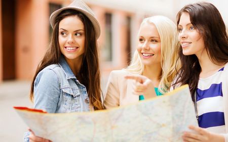 lost city: holidays and tourism concept - beautiful girls looking for direction in the city Stock Photo
