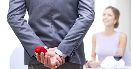 부부, 사랑, 제안 및 휴가 개념 - 가까운 레스토랑에서 여자에서 뒤에 빨간색 상자를 숨기는 남자의 닫습니다