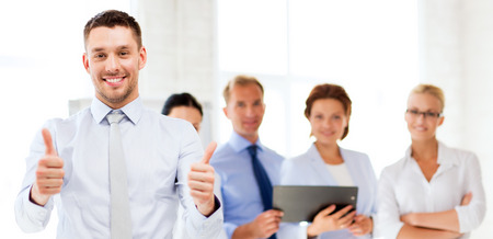 group  accountant: attractive businessman in office showign thumbs up