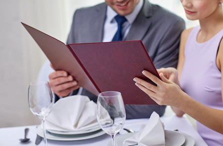 restaurant, food, eating and holiday concept - close up of happy couple with menu choosing dishes at restaurant Stock Photo