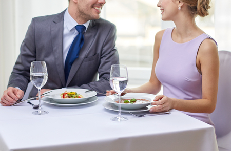 up to date: restaurant, food, people, date and holiday concept - close up of happy couple talking at restaurant Stock Photo