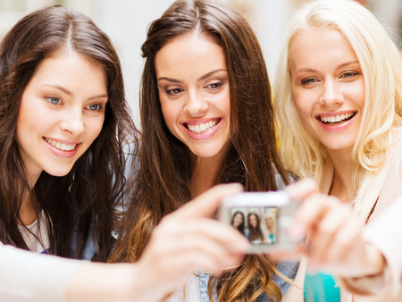 holidays and tourism concept - beautiful girls taking picture in cafe in city Imagens