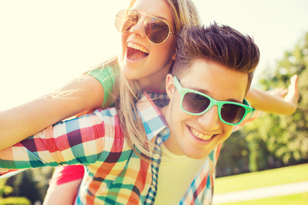 out in town: holidays, vacation, love and friendship concept - smiling couple having fun in park Stock Photo
