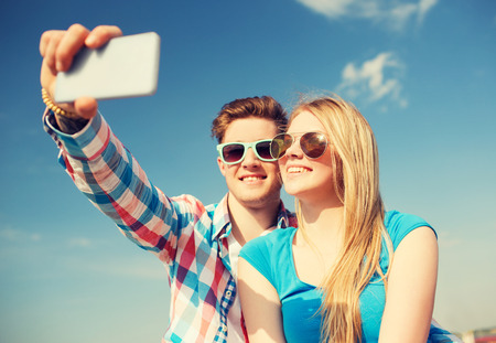 haciendo el amor: d�as de fiesta, vacaciones, el amor y la amistad concepto - sonriente pareja que se divierten al aire libre Foto de archivo
