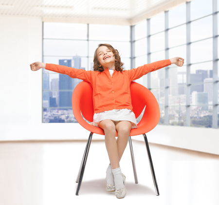 spreaded: people, happiness, childhood and furniture concept - happy little girl sitting on chair with spreaded arms over empty living room background
