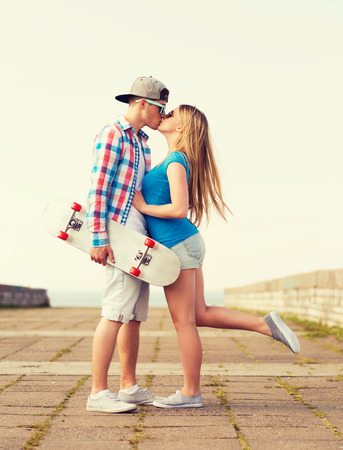 women kissing women: holidays, vacation, love and friendship concept - smiling couple with skateboard kissing outdoors Stock Photo
