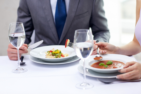 restaurant, food, people, date and holiday concept - close up of couple eating appetizers at restaurant photo
