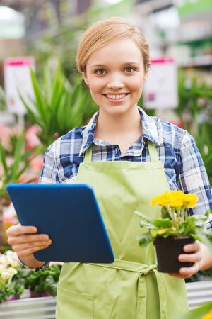 horticulture: people gardening technology and profession concept  happy woman or gardener with tablet pc computer and flowers in greenhouse Stock Photo