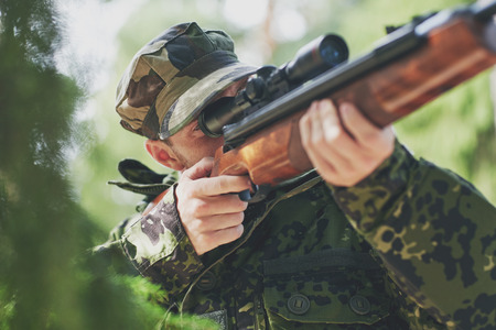 hunting rifle: hunting war army and people concept  young soldier ranger or hunter with gun walking in forest Stock Photo