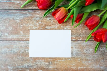 floristics: advertisement valentines day greeting and holidays concept  close up of red tulips and blank paper or letter on wooden background