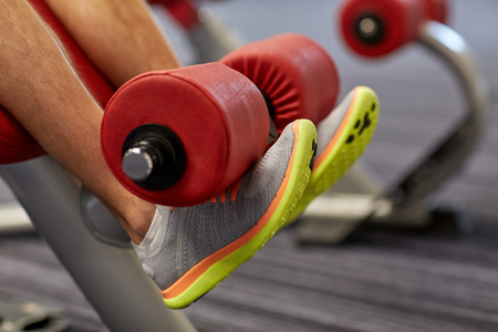 sport fitness bodybuilding lifestyle and people concept close up of man legs exercising on gym machine