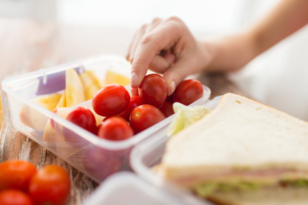 eating up: healthy eating storage dieting and people concept  close up of woman with food in plastic container at home kitchen