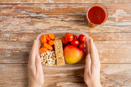 diet food: healthy eating dieting and people concept  close up of woman hands with food in plastic container and fresh tomato juice at home kitchen