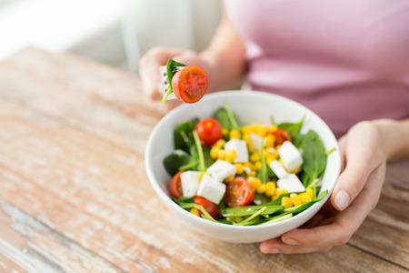 Alimentación saludable dieta y el concepto de la gente cerca de la mujer joven que come ensalada de verduras en casa Foto de archivo - 40525846