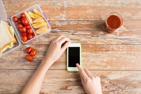 dieta saludable: tecnología de la dieta de alimentación saludable y la gente concepto de cerca de manos de mujer con teléfono inteligente en blanco y los alimentos en un recipiente de plástico sobre la mesa en casa