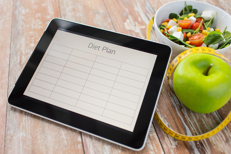 diet plan: healthy eating dieting and weigh loss concept  close up of diet plan on tablet pc screen green apple measuring tape and sald