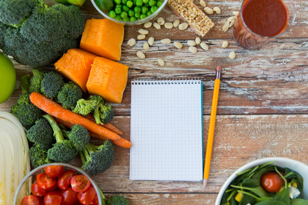 healthy eating vegetarian food advertisement and culinary concept  close up of ripe vegetables and notebook with pencil on wooden table Archivio Fotografico