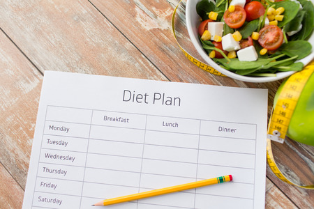 healthy eating dieting slimming and weigh loss concept  close up of diet plan paper green apple measuring tape and salad