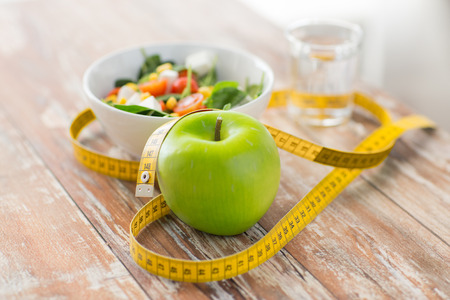 home  life: healthy eating dieting slimming and weigh loss concept  close up of green apple measuring tape and salad