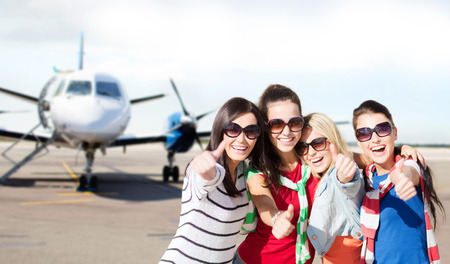 summer holidays vacation travel and people concept  happy teenage girls in sunglasses or young students showing thumbs up over airport background