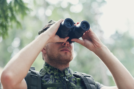 observing: hunting war army and people concept  young soldier ranger or hunter with binocular observing forest