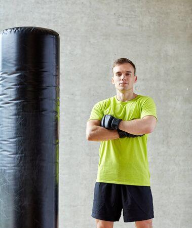 artes marciales: el deporte, la caja y la gente concepto - hombre joven con guantes de boxeo y saco de boxeo en el gimnasio Foto de archivo