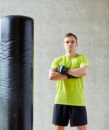 arts: sport, box and people concept - young man with boxing gloves and punching bag in gym