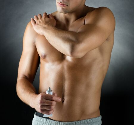 muscle tension: sport bodybuilding medicine and people concept  young man standing over black background and applying pain relief gel on his shoulder