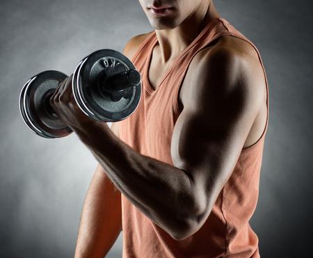 muscle: entrenamiento de culturismo el deporte y el concepto de la gente joven con mancuernas flexionando los músculos sobre fondo gris