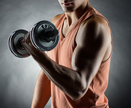man arm: sport bodybuilding training and people concept  young man with dumbbell flexing muscles over gray background