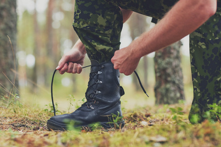 army boots: war hiking army and people concept  close up of soldier boots and hands tying bootlaces in forest Stock Photo