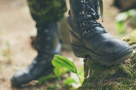 uniform green shoe: war hiking army and people concept  close up of soldier feet in army boots in forest