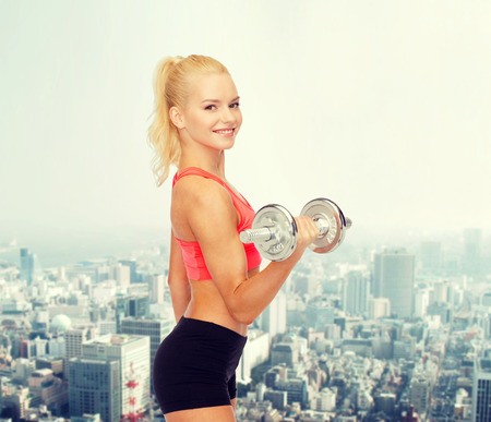 fitness healthcare and exercise concept  young sporty woman with heavy steel dumbbell