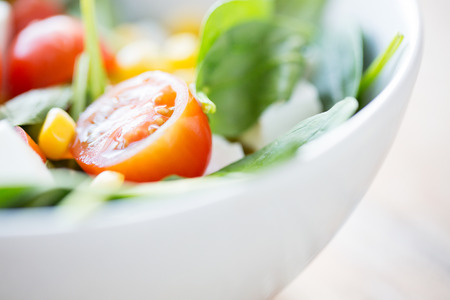 eating up: healthy eating dieting vegetarian kitchen and cooking concept  close up of vegetable salad bowl at home