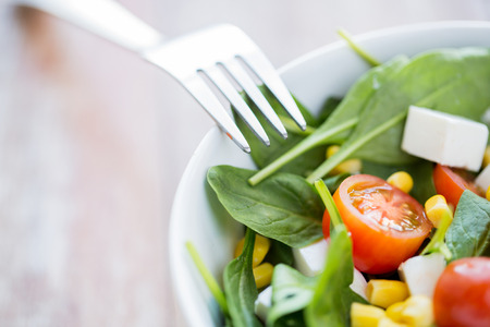 healthy eating dieting vegetarian kitchen and cooking concept  close up of vegetable salad bowl and fork at home