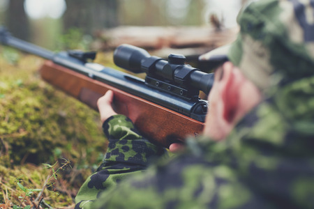 firing: hunting war army and people concept  young soldier ranger or hunter with gun walking in forest Stock Photo