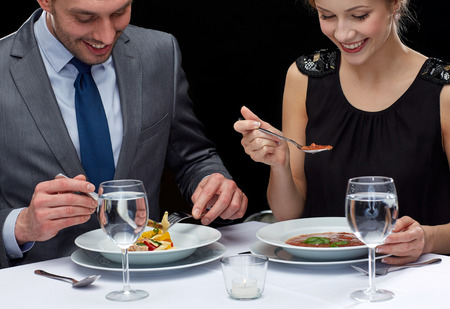 up to date: restaurant food people date and holiday concept  close up of happy couple eating at restaurant Stock Photo