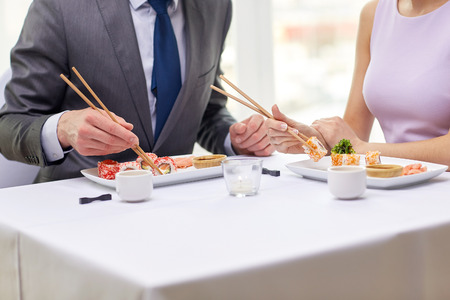 dinner date: restaurant food people date and holiday concept  close up of couple eating sushi at restaurant