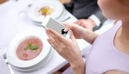 dattes: les gens loisir de manger et de concept technologique close up d'un couple avec les smartphones prenant l'image de la nourriture au restaurant Banque d'images