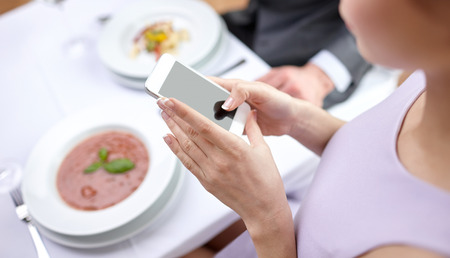 family indoors: people leisure eating and technology concept  close up of couple with smartphones taking picture of food at restaurant