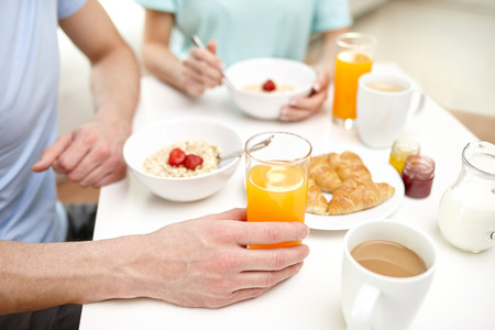 having breakfast: food eating people and healthy food concept  close up of couple having breakfast at home Stock Photo