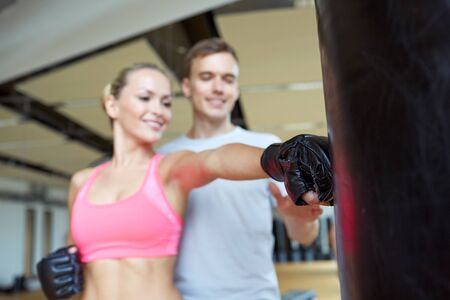 sport fitness lifestyle and people concept  happy woman with personal trainer boxing punching bag in gym photo