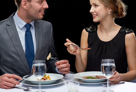 up to date: restaurant food people date and holiday concept  close up of happy couple talking at restaurant Stock Photo