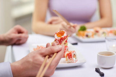 up to date: restaurant food people date and holiday concept  close up of couple eating sushi at restaurant