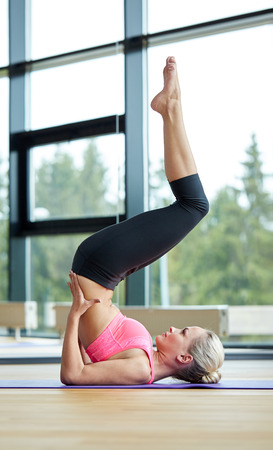 perfect fit: fitness sport training and people concept  woman doing shoulderstand on mat in gym Stock Photo