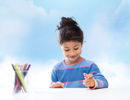 asian art: children, creativity and happy people concept - happy little girl drawing with coloring pencils over blue sky background